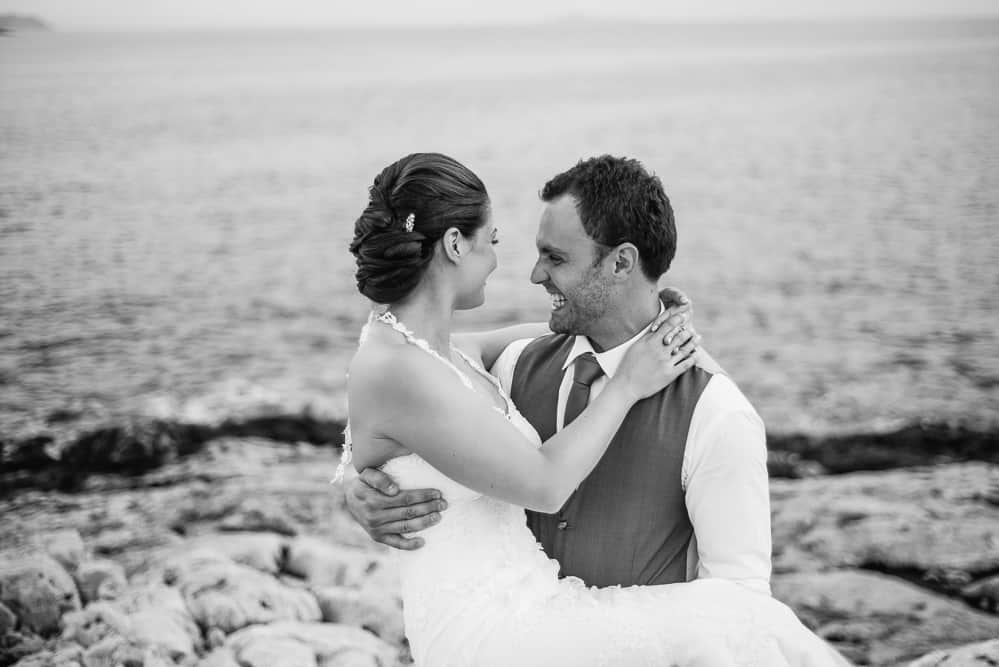 Groom carries his bride on their seaside destination wedding