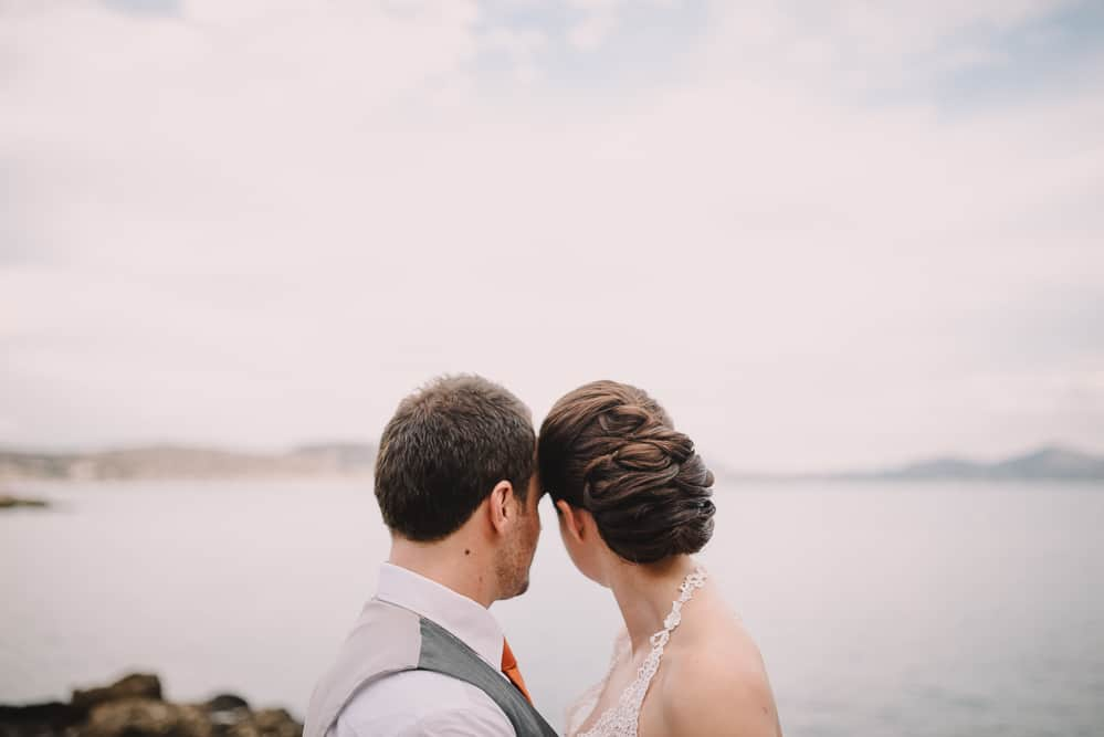 Newly weds look out to sea with stunning bridal hair by Gemma Sutton for destination wedding