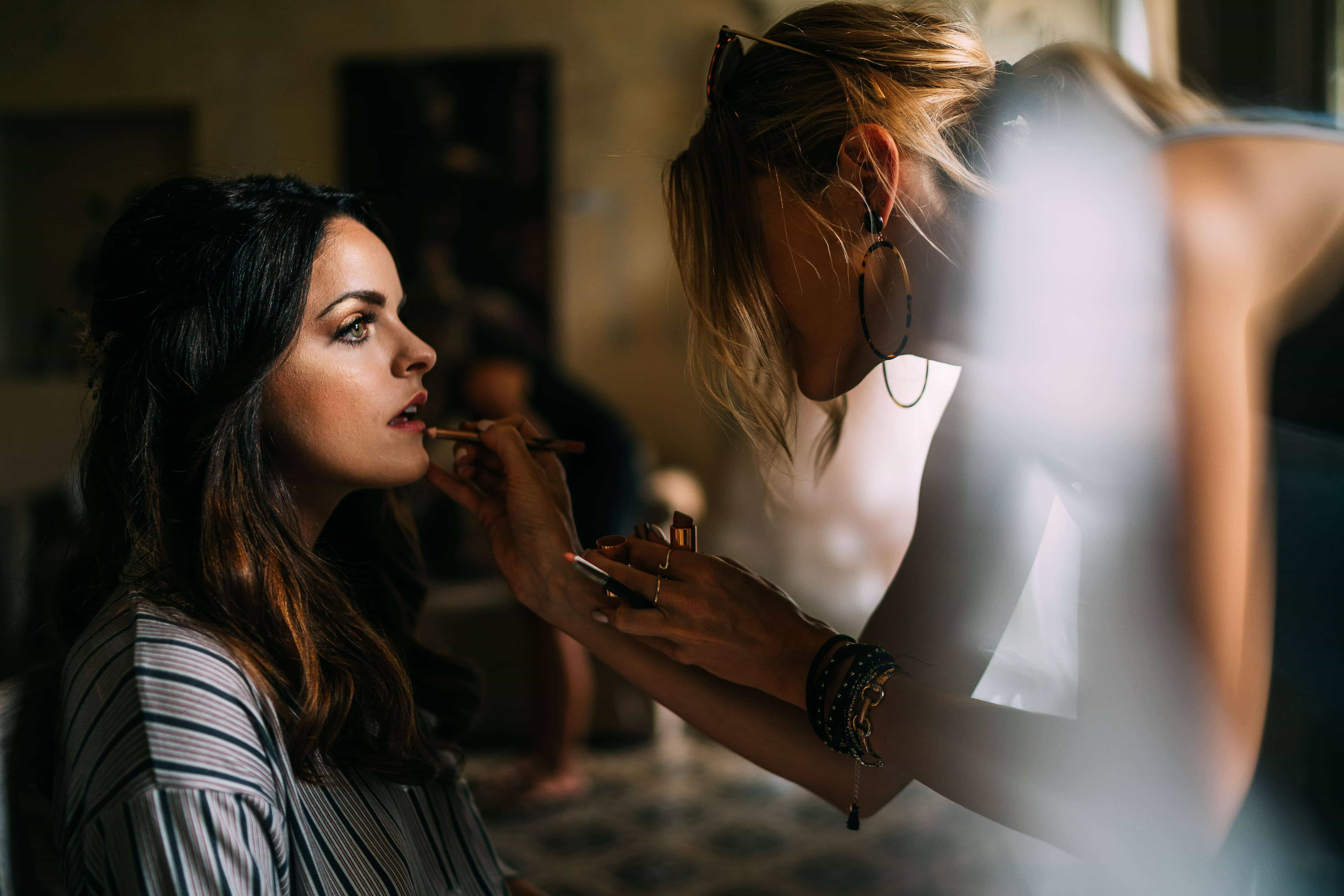 Gemma applies a red lipstick to bride Sarah at her Lake Como Wedding