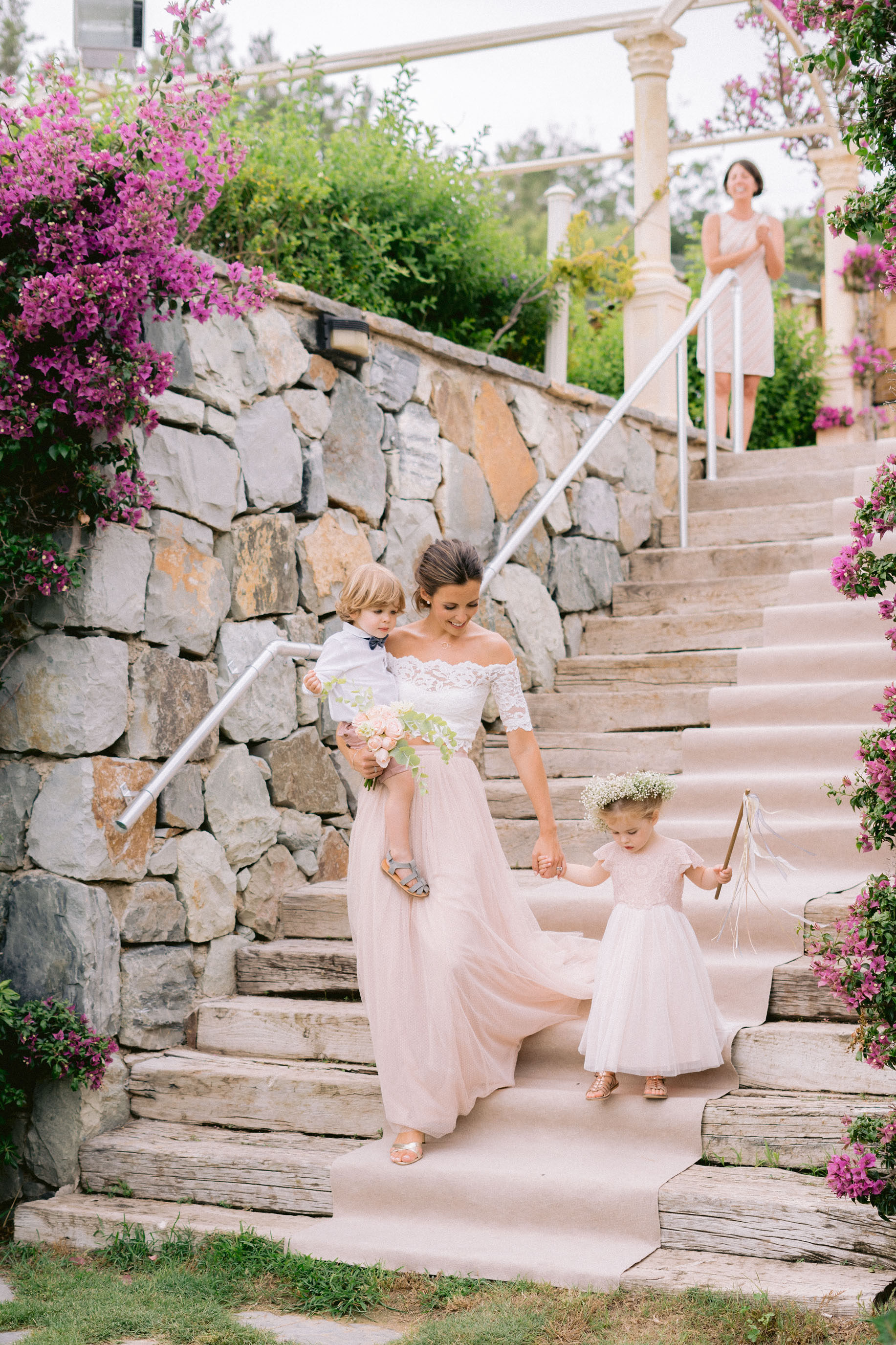 Beautiful sister of the bride and maid of honour Therese walks down  rustic Turkish steps  with page boy Harrison and little flower girl, Therese has a volumous up-do and flowing dress