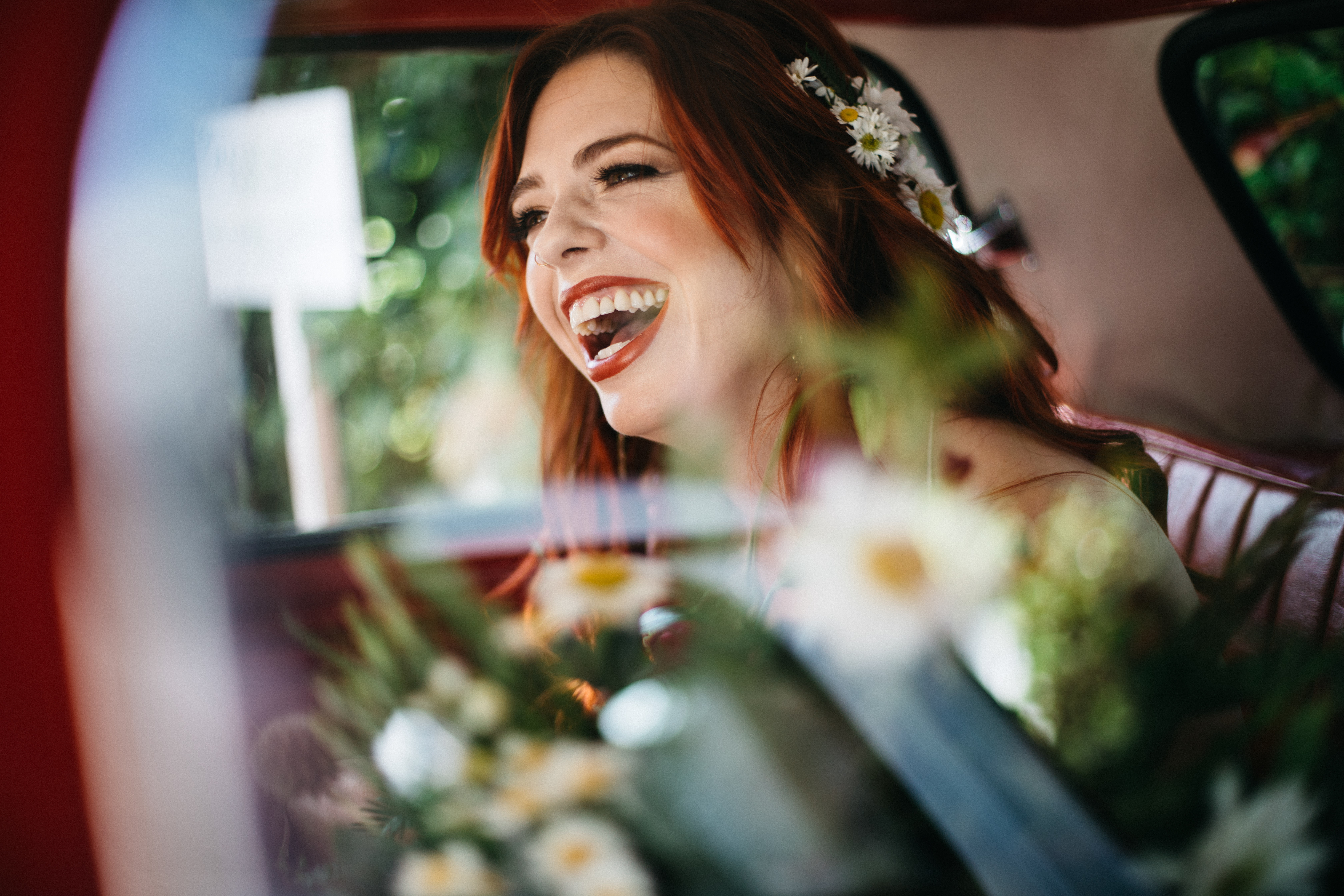 exuberant redhead bride laughs on her wedding morning with stunning shasta daisies in her hair