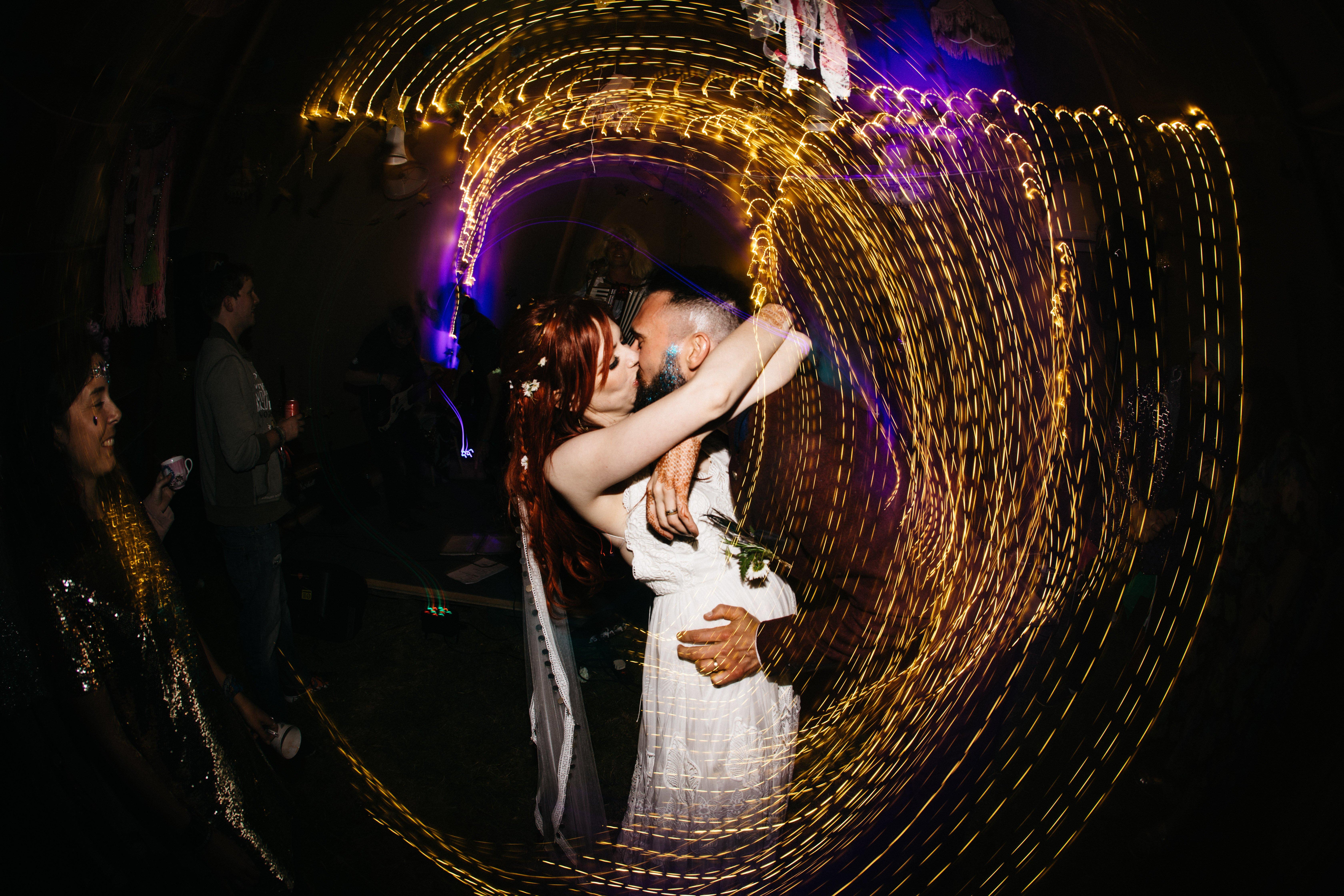 Redhead bride Fern kissing Adam, her groom, at their festival wedding
