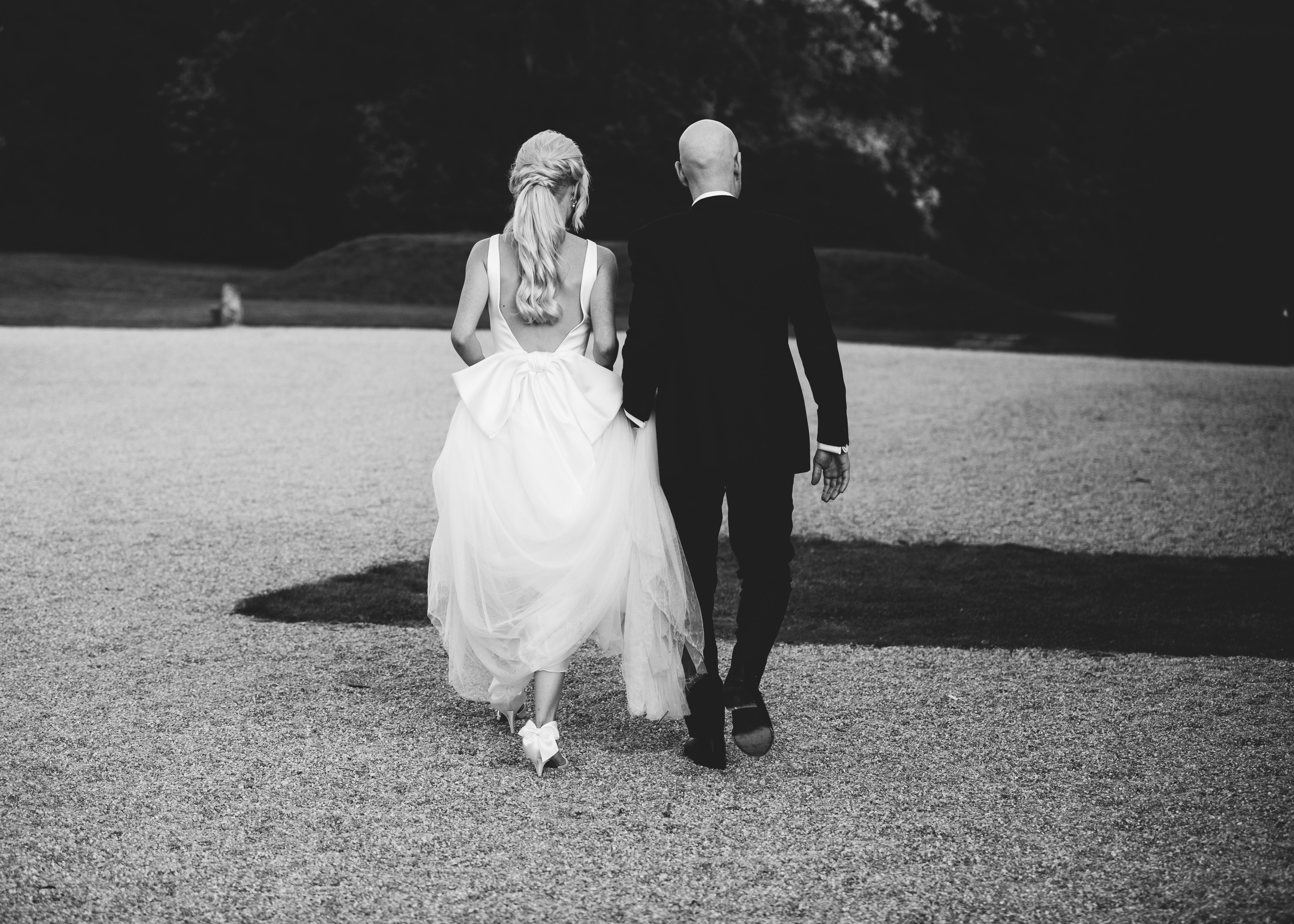 bride and groom walk together with her gorgeous ponytail and beautiful big bowed dress